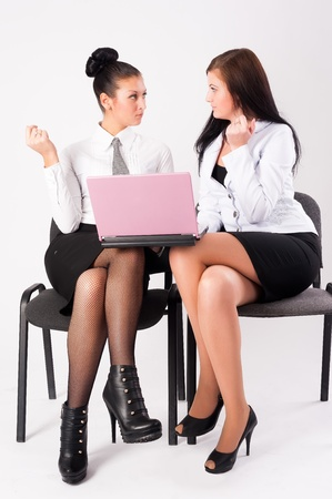 Two young businesswoman with laptop at white background photo