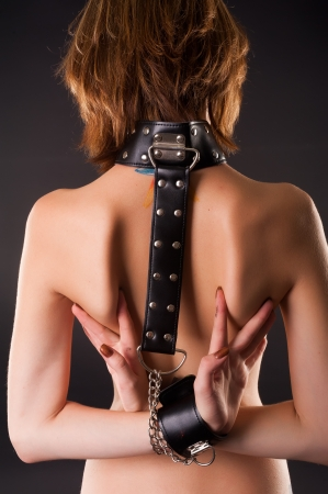 Back view of attractive topless woman with handcuffs  Bondage concept  Studio shot at black background