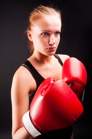 Young attractive woman with boxing gloves at black background photo