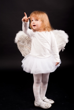 Two years old baby girl wearing white angel wings over black background  photo