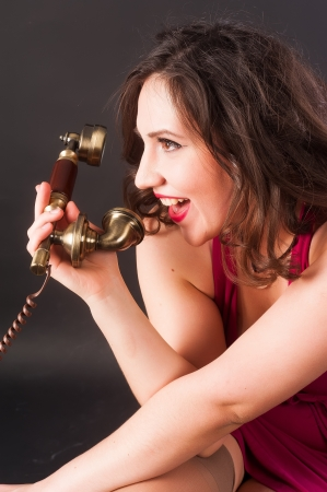 Young attractive woman cries into phone at black background photo
