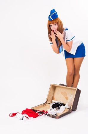 Attractive young stewardess with old suitcase at white background photo