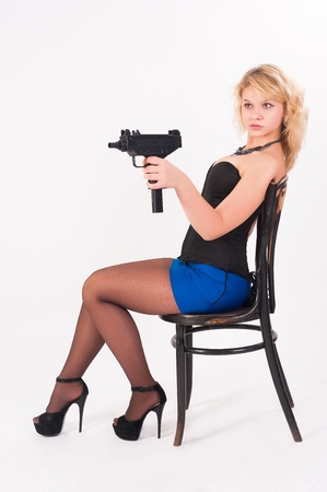 Young beautiful woman with gun sitting on chair  Isolated on white photo