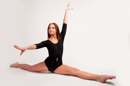 Fit young woman doing stretching exercise at white background photo