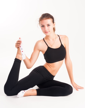 Fit young woman doing stretching exercise  Isolated on white photo