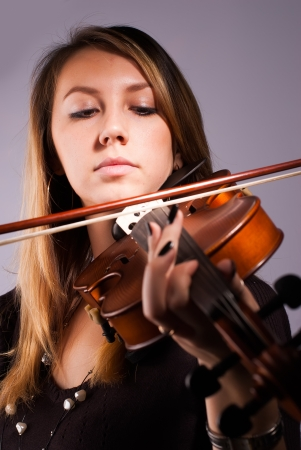 Young pretty woman playing music by violin Stock Photo - 18622144