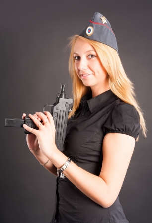 Sexy young woman with a gun at black  Focus on gun photo