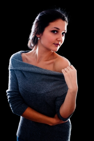 flirtatious: Young beautiful woman in sweater  Isolated on black