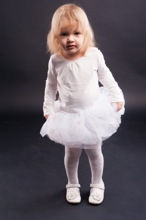 Two years old baby girl wearing white suit at black background  photo