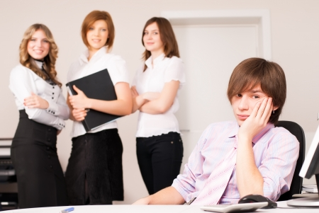 Businessman leading team of business ladies in office photo