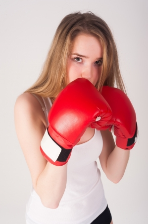Young blonde woman with boxing gloves on white background
