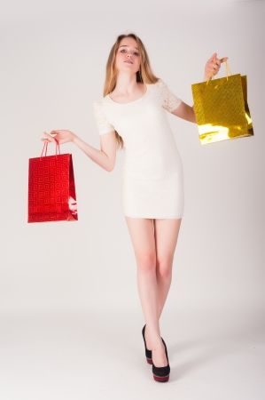 Young attractive woman holding bags at white background  photo