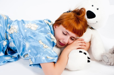 Young attractive woman sleeping with white bear toy photo