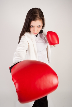 Serious business lady with red gloves fighting against white background photo
