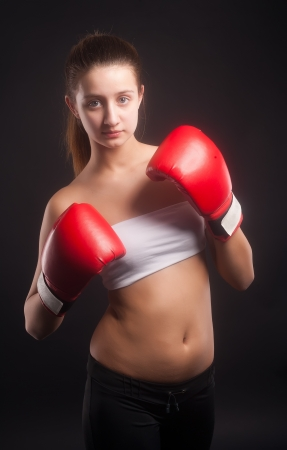 Young beautiful boxer woman with red boxing gloves over black background photo