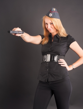 elegant lady in black holding gun and aiming photo