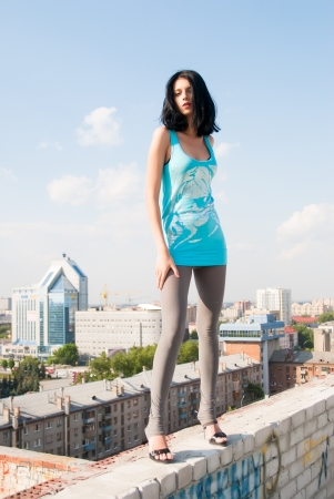 Beautiful woman standing on the rooftop of residental building photo