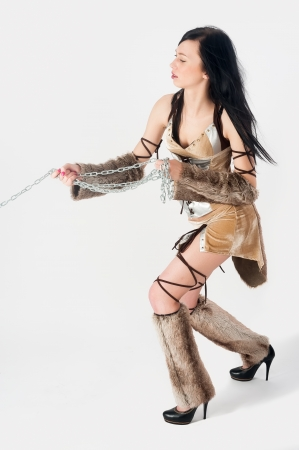 Young beautiful woman in warrior role with chains at white background photo