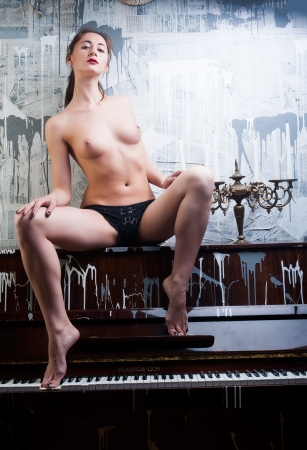 Beautiful young topless woman sitting on old piano Stock Photo