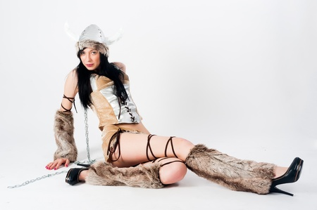 Young attractive woman in barbarian costume at white background photo