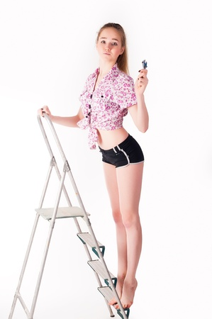 studio shot of a woman standing on ladder with wrench photo