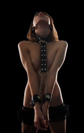 Attractive topless woman with handcuffs  Bondage concept  Studio shot at black background