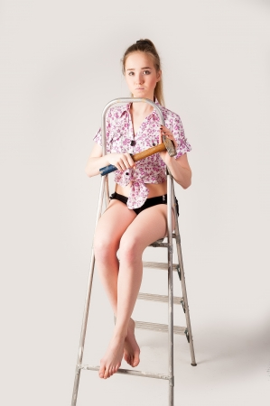 studio shot of a woman sitting on ladder with hammer photo
