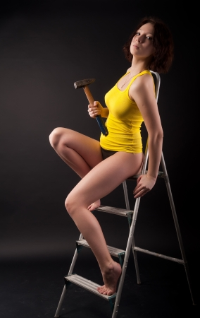 studio shot of a woman in yellow vest on ladder with hammer at black background