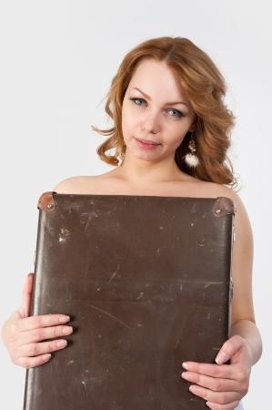 sexy woman standing: joven y sexy mujer de pie cubriendo su cuerpo por la vieja maleta en el fondo blanco