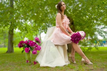 Portrait of a beautiful blonde woman with peony flowers at nature background photo