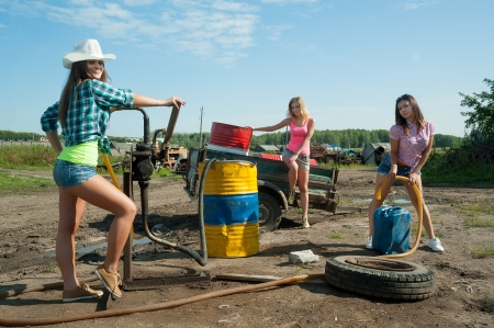 gasoil: Attractive women near old gas station which located in outback