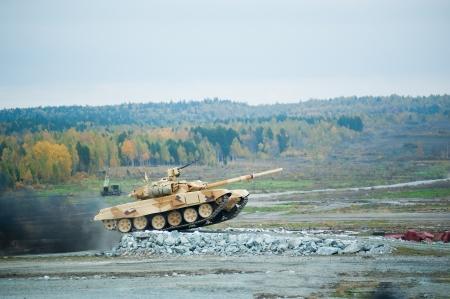 Russische militaire tank T-90S met overwinnen van de hindernis