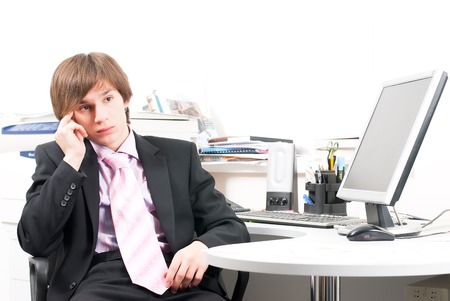 Young businessman working in office, sitting at desk photo