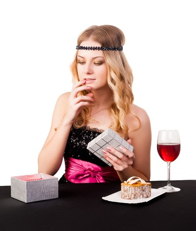 Pretty woman with cake dessert and glass wine  She surprised by received gift photo