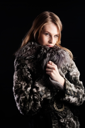 beautiful woman in a fur coat at black background photo