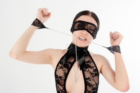 Shot of a sexy woman in black lingerie with handcuffs over white background  photo