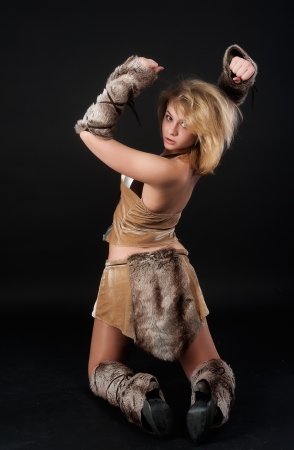 Young beautiful woman in barbarian costume at black background photo