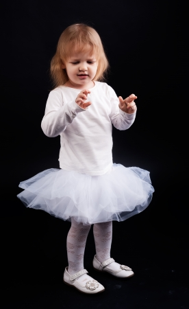 crossing fingers: Two years old baby girl wearing white suit and crossing fingers at black background