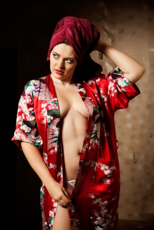 beautiful young woman wearing a towel and bathrobe at room background photo
