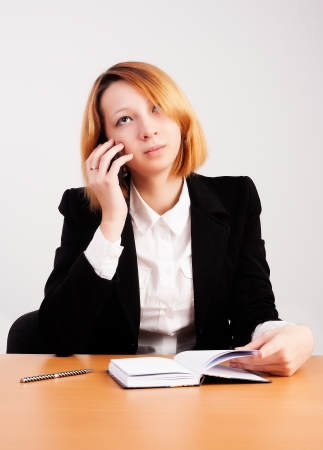 Beautiful business woman talking by cell phone in office photo