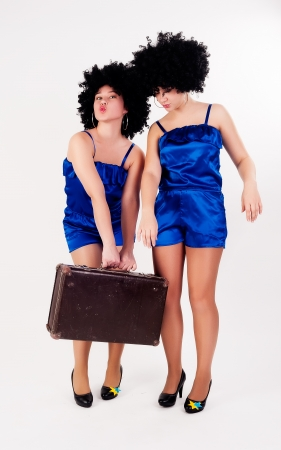 Young beautiful women dancing in disco style with old suitcase photo