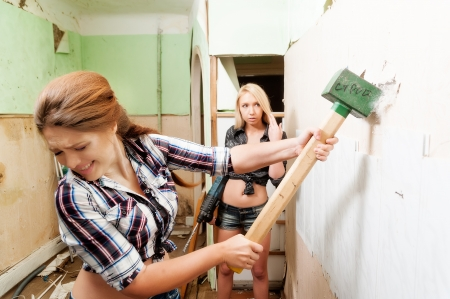 Two attractive women with sledge hammer and puncher making home improvement photo