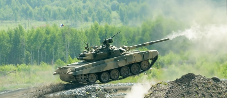 Shooting tank T-80 moving through cross-country terrain with obstacles Stock Photo