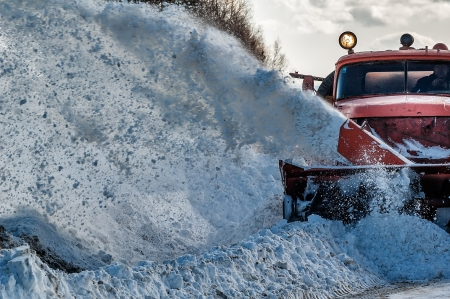 Machinery with snowplough cleaning road by removing snow from intercity highway after winter blizzard photo