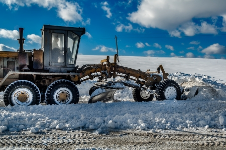 Grader removes snow from road after storm
