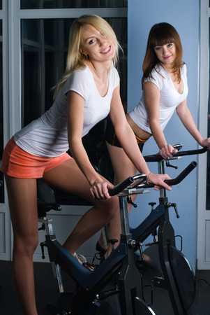 simulators: Young women on bicycle simulators in fitness center