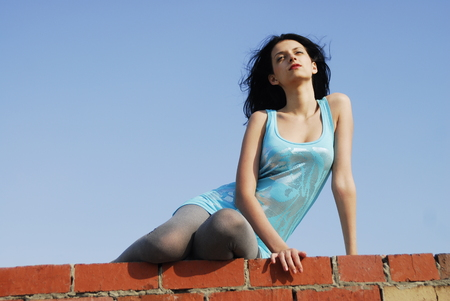 Young woman resting on residential building roof photo