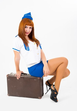 Attractive young stewardess sitting on old-fashioned suitcase at white background photo
