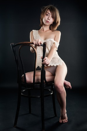 beautiful brunette woman in fishnet top and lingerie sitting on chair photo