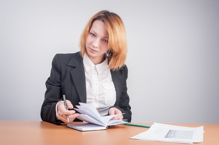 caucasian businesswoman sitting at desk in casual clothes and working with dayly log photo